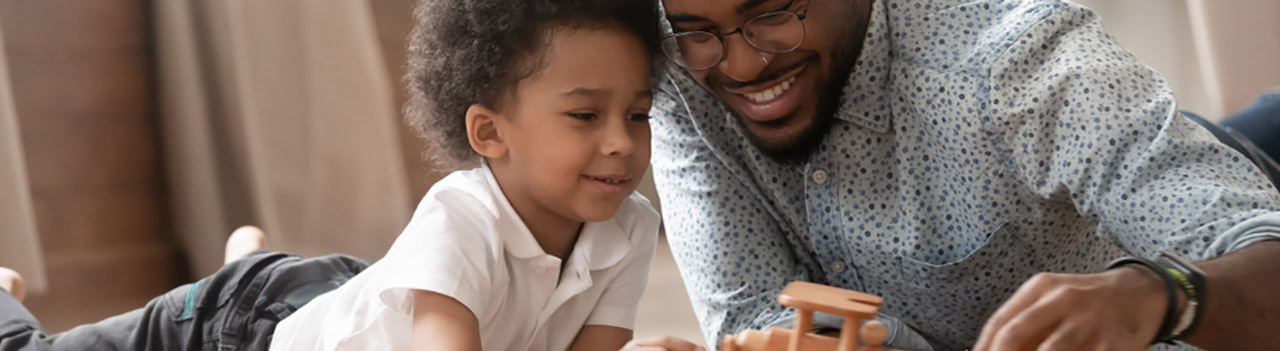 African-American-father-and-young-son-playing-with-wooden-airplane