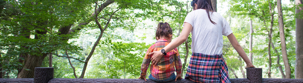 mom-and-daughter-sitting-on-a-fence-in-forest