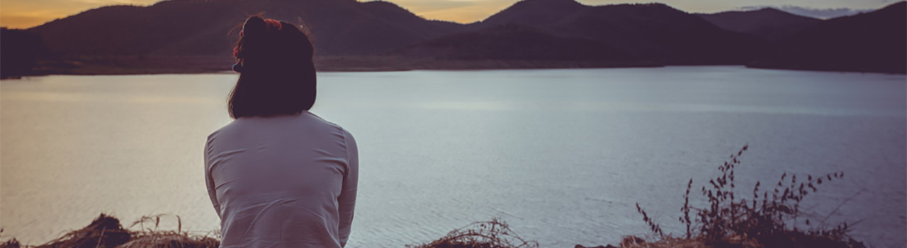 woman-gazing-at-sunset-with-mountain-backdrop